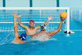 Front view of young water polo players having goal action