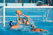 Shot of young water polo players having goal action