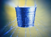 Water poring through holes in bucket, close-up