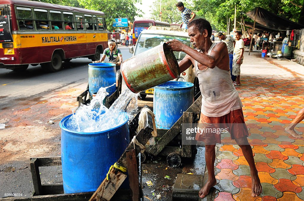 Water porters working to meet up a huge water demand in Babughat Bus stand area on a hot summer day on May 28, 2015 in Kolkata, India.