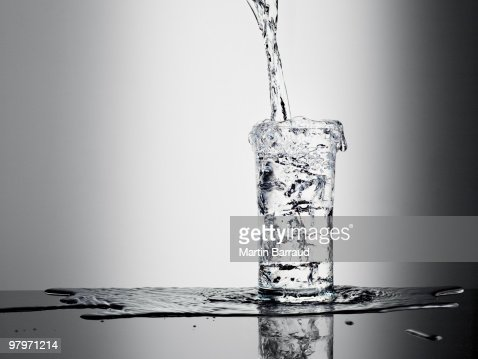 Water pouring into glass and overflowing