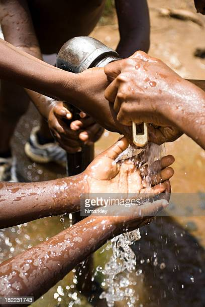 Water Pouring out of a Pump Over African Children's Hands