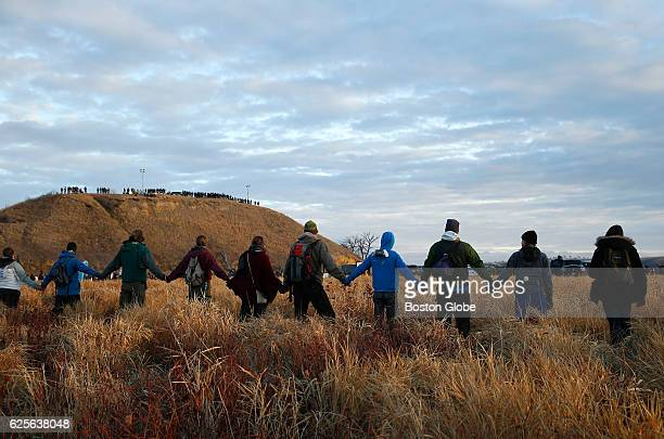 Water protectors join hands in prayer at the end of the day's protest as police line the hill at Standing Rock on Nov 24 during an ongoing dispute...