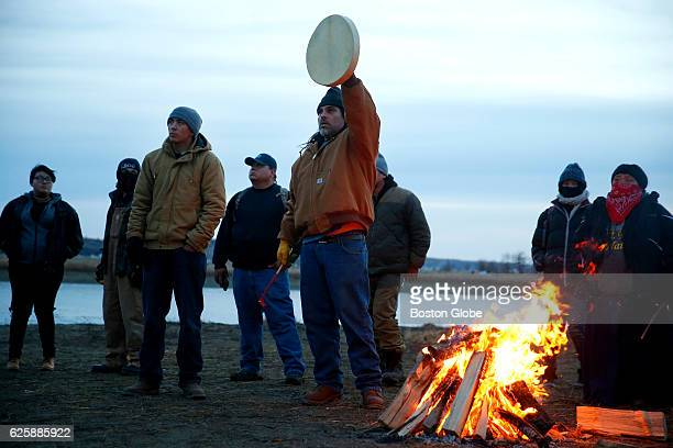 Water protectors sing in opposition to police lining the hill top on Turtle Island in Cannon Ball ND near Standing Rock on Nov 25 during an ongoing...