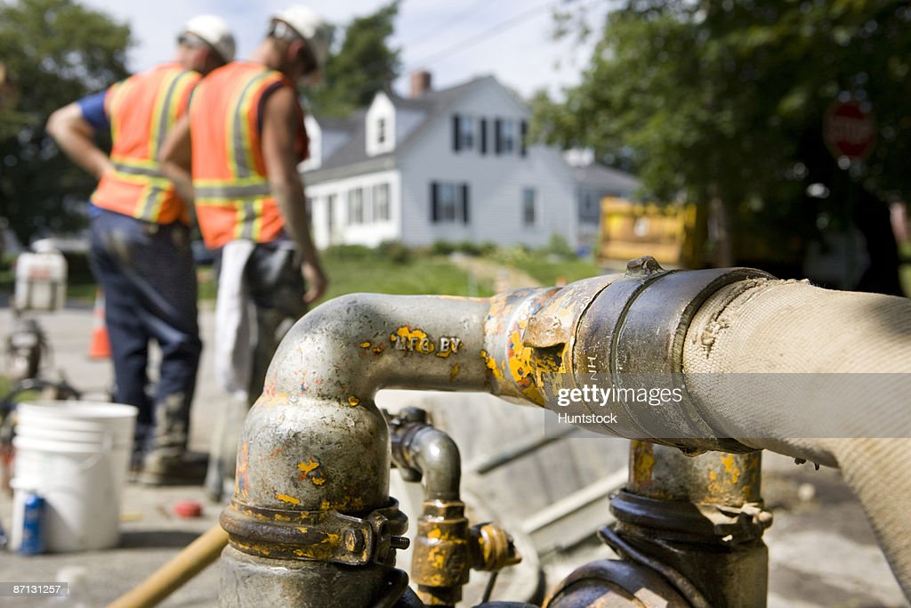 Water pump on construction site, two workers in background