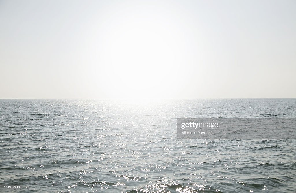 water reflecting the sun as it rises above horizon : Stock Photo