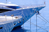 the bows of luxury yachts moored  with refection of water