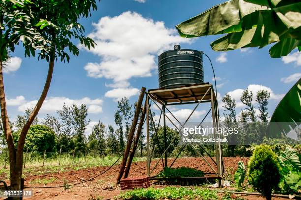 A Water Reservoir on a water tower next to a field of a farm on which plants grow with the support of the irrigation system of local farming...
