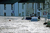 Water rises above cars as flooding blights the market town of Cockermouth at the confluences of the River Cocker and River Derwent which are...