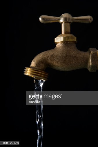 Water running from faucet against black background stock photo getty images - How to run plumbing collection ...