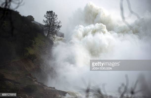 Water rushes down a spillway as an emergency measure at the Oroville Dam in Oroville California on February 13 2017 Almost 200000 people were under...