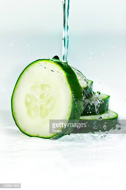 Water splashing over slices of cucumber
