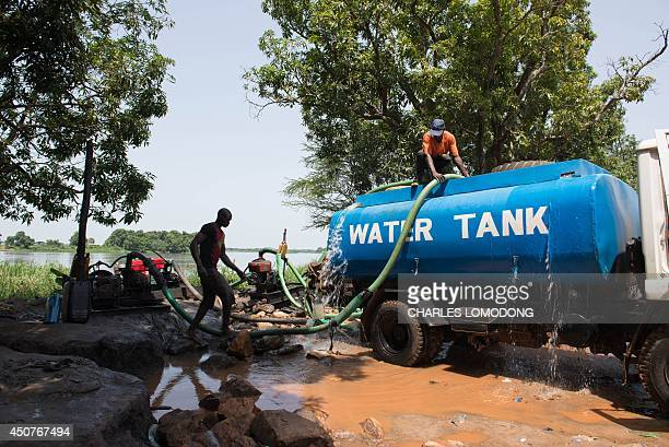 A water tanker operator pours a ready mixed chlorine water treatment in his tanker to treat the water before distribution on June 17 2014 near Juba...