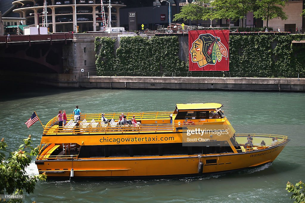 A water taxi passes by a Chicago Blackhawks' banner on the Chicago River in the Loop on June 12, 2013 in Chicago, Illinois. The Chicago Blackhawks will match up against the Boston Bruins tonight at the United Center in the first game on the NHL Stanley Cup playoffs.