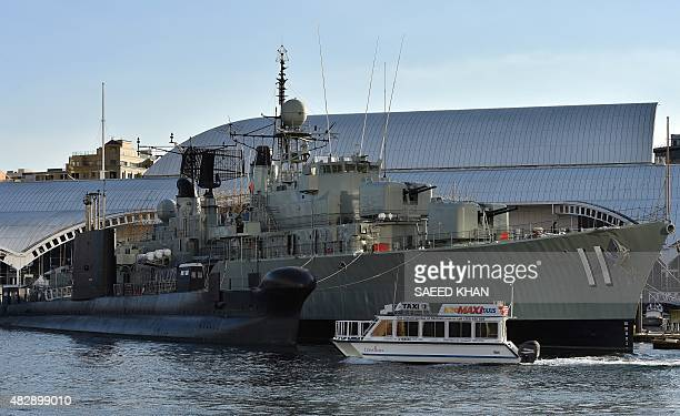 A water taxi sails past the submarine HMAS Onslow and the destroyer HMAS Vampire preserved as museum ships in front of the National Maritime Museum...