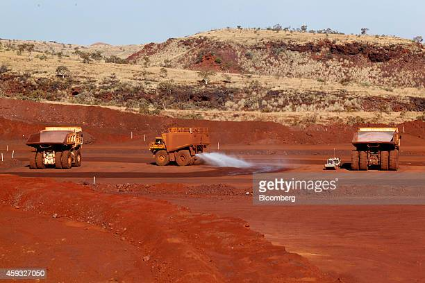 A water truck sprays water onto the Delta 1 mine pit as dump trucks stand nearby at Hancock Prospecting Pty's Roy Hill Mine operations under...