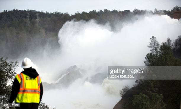 A water utility worker looks towards discharging water as it is released down a spillway as an emergency measure at the Oroville Dam in Oroville...