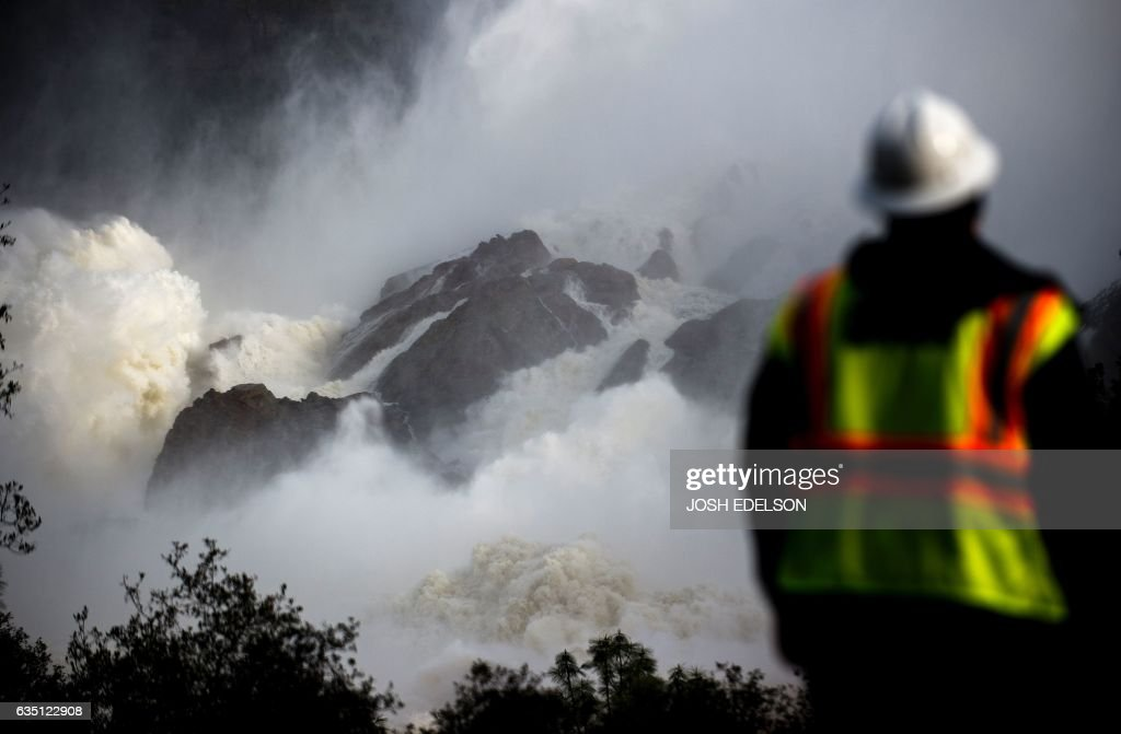 A water utility worker looks towards discharging water as it is released down a spillway as an emergency measure at the Oroville Dam in Oroville, California on February 13, 2017. Almost 200,000 people were under evacuation orders in northern California Monday after a threat of catastrophic failure at the United States' tallest dam. Officials said the threat had subsided for the moment as water levels at the Oroville Dam, 75 miles (120 kilometers) north of Sacramento, have eased. But people were still being told to stay out of the area. / AFP / Josh Edelson