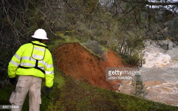 A water utility worker peers over an eroded hillside as rushing water discharges down a spillway as an emergency measure at the Oroville Dam in...