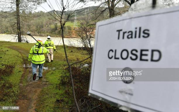 Water utility workers work their way down to an eroded hillside to measure depth as rushing water discharges down a spillway as an emergency measure...