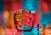 Glass with water on colorful bokeh background