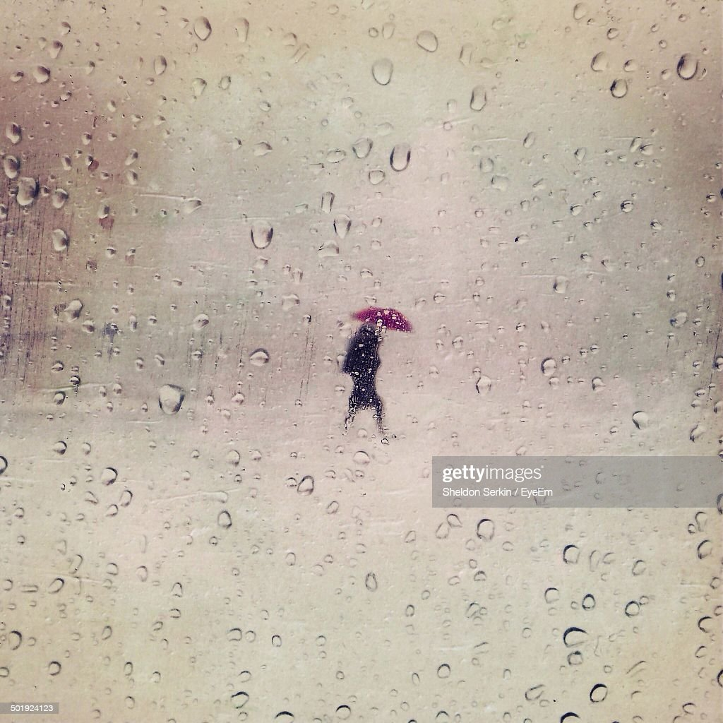 Waterdrops on glass and woman with umbrella