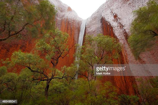 A waterfall is seen in Kantju Gorge as it rains at Uluru on November 27 2013 in UluruKata Tjuta National Park Australia Uluru/ Ayers Rock is a large...