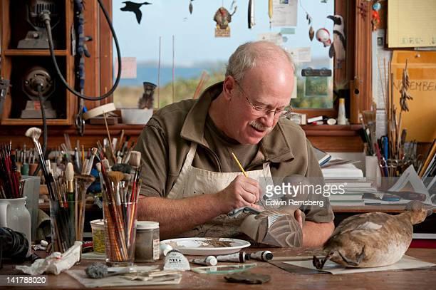 Waterfowl decoy carver demonstrating his craft.