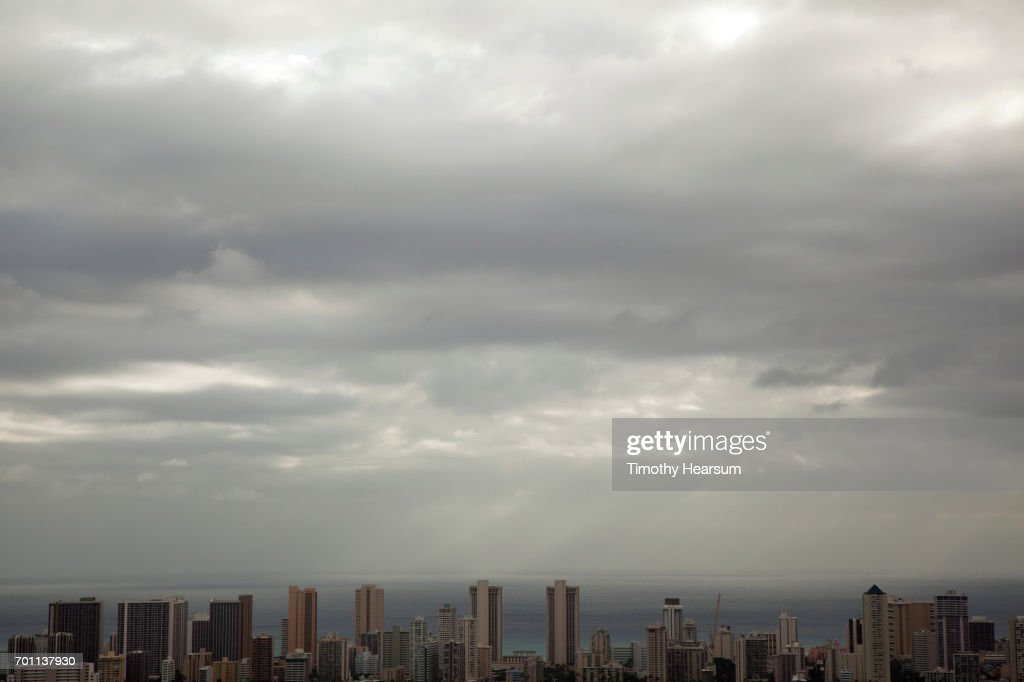 Waterfront buildings with ocean and cloudy sky beyond : Stock Photo