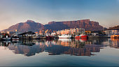 Early morning lighting on the waterfront and Table Mountain creates a perfect reflection in the harbour water infront of it. With fishing boads in the foreground and the City of Cape Town behind the w