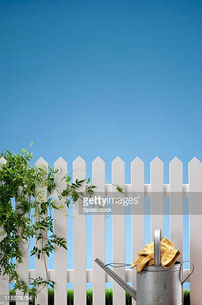 Watering Can And Gloves With White Fence
