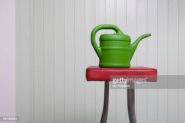 A watering can on a stool