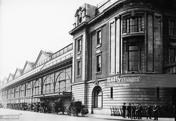 Waterloo Station 1910 A line of cars and two horse drawn carriages outside the station A group of porters with their trolleys can be seen in the...