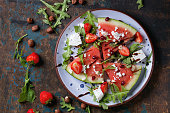 Blue spotted plate with watermelon and strawberry fruit salad with feta cheese, arugula, nuts and balsamic sauce, served over old dark wood background. Top view. Healthy eating concept