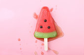 watermelon shaped ice cream pop lay on pink pastel background