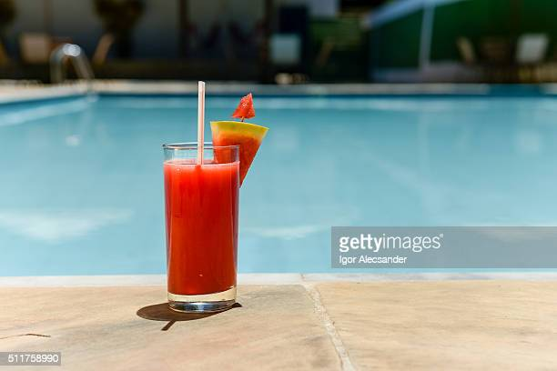 Watermelon tropical drink at the edge of a swimming in a summer sunny day
