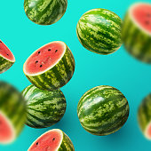 Delicious and juicy sweet watermelons sliced and whole on a turquoise summer background.