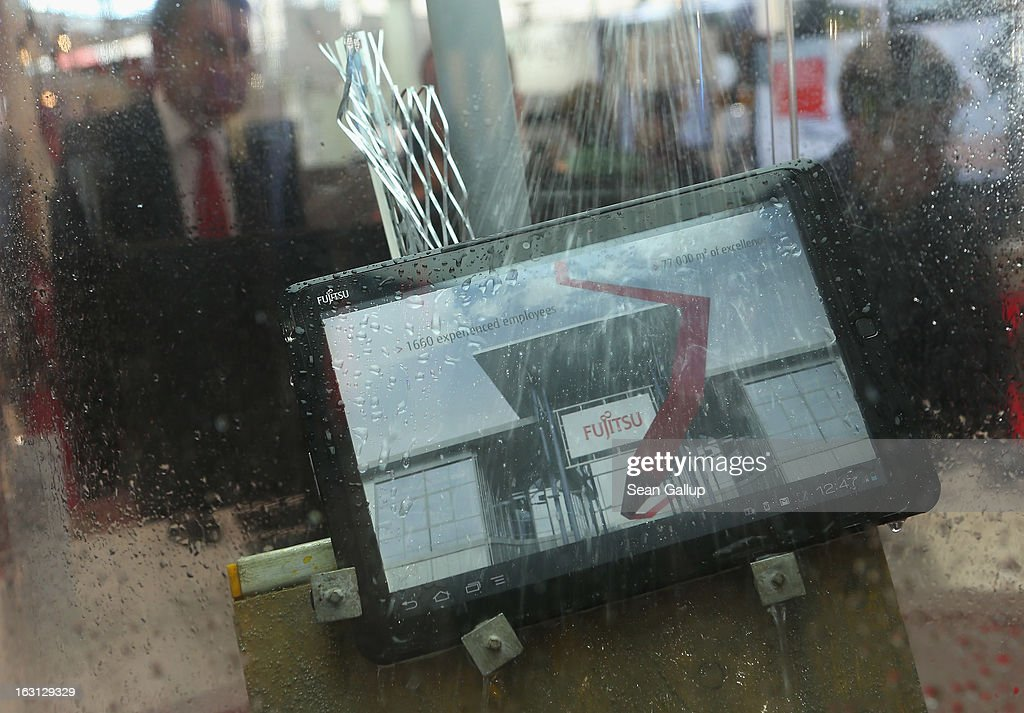 A waterproof tablet computer gets sprayed with water at the Fujitsu stand at the 2013 CeBIT technology trade fair on March 5, 2013 in Hanover, Germany. CeBIT will be open March 5-9.