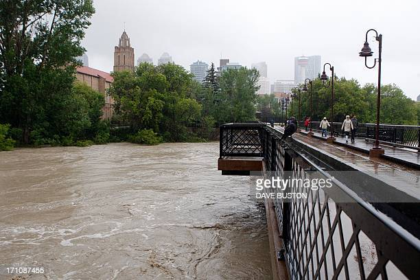Waters rise around a footbridge in Calgary Alberta Canada June 21 2013 Flooding forced the evacuation of some 100000 people in the western city of...