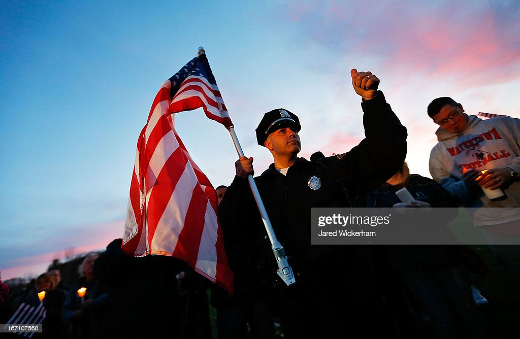 Watertown Police officer Brandon O'Neill acknowledges the crowd while carrying a large American flag during a candlelight vigil at Victory Park on April 20, 2013 in Watertown, Massachusetts. A manhunt for Dzhokhar A. Tsarnaev, 19, a suspect in the Boston Marathon bombing ended after he was apprehended on a boat parked on a residential property in Watertown, Massachusetts. His brother Tamerlan Tsarnaev, 26, the other suspect, was shot and killed after a car chase and shootout with police. The bombing, on April 15 at the finish line of the marathon, killed three people and wounded at least 170.