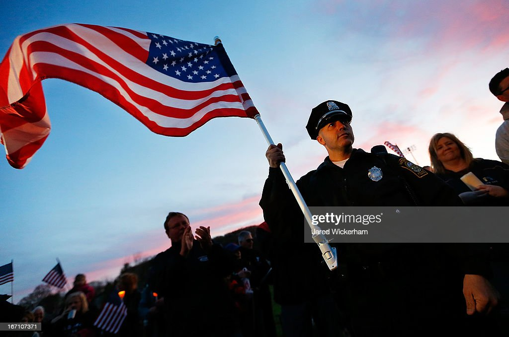 Watertown Police officer Brandon O'Neill holds a large American flag during a candlelight vigil at Victory Park on April 20, 2013 in Watertown, Massachusetts. A manhunt for Dzhokhar A. Tsarnaev, 19, a suspect in the Boston Marathon bombing ended after he was apprehended on a boat parked on a residential property in Watertown, Massachusetts. His brother Tamerlan Tsarnaev, 26, the other suspect, was shot and killed after a car chase and shootout with police. The bombing, on April 15 at the finish line of the marathon, killed three people and wounded at least 170.
