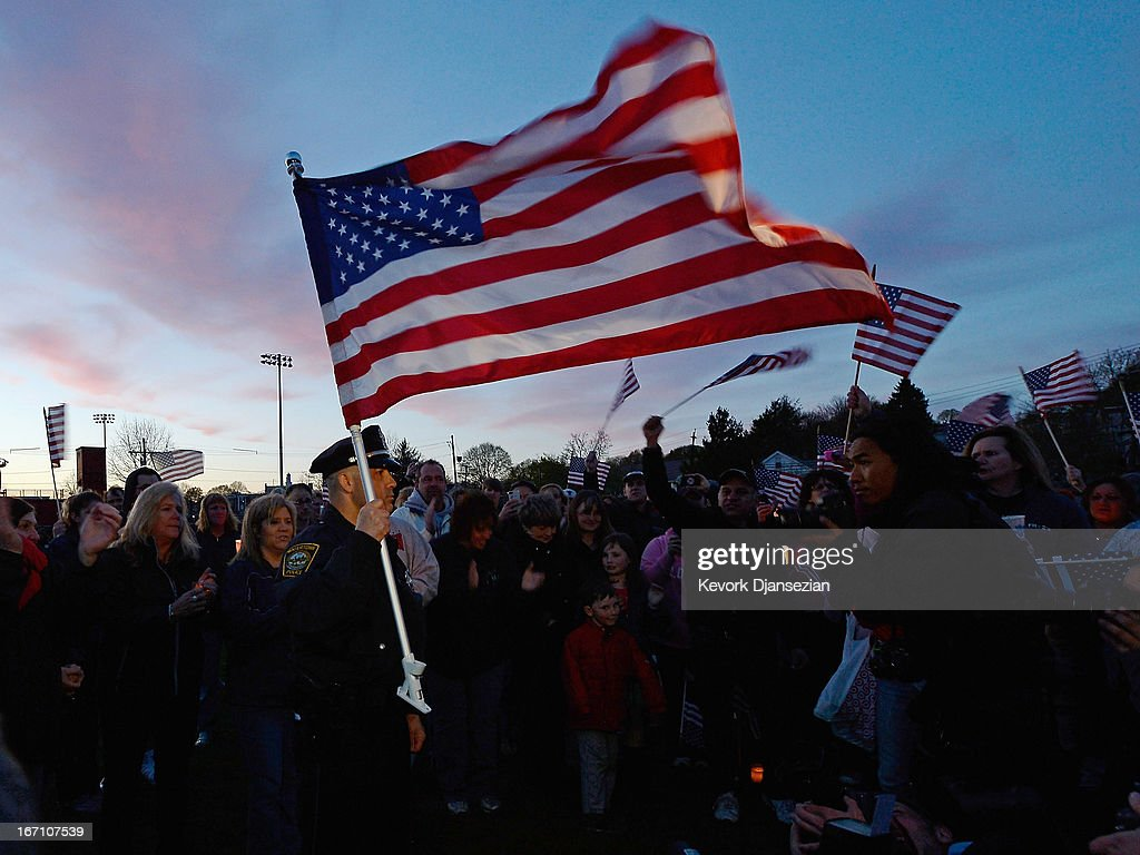 Watertown Police officer Brandon O'Neill holds a large U.S. flag during a candlelight vigil for victims of the Boston Marathon bombing at Victory Park on April 20, 2013 in Watertown, Massachusetts. A manhunt for Dzhokhar A. Tsarnaev, 19, a suspect in the Boston Marathon bombing ended after he was apprehended on a boat parked on a residential property in Watertown, Massachusetts. His brother Tamerlan Tsarnaev, 26, the other suspect, was shot and killed after a car chase and shootout with police. The bombing, on April 15 at the finish line of the marathon, killed three people and wounded at least 170.