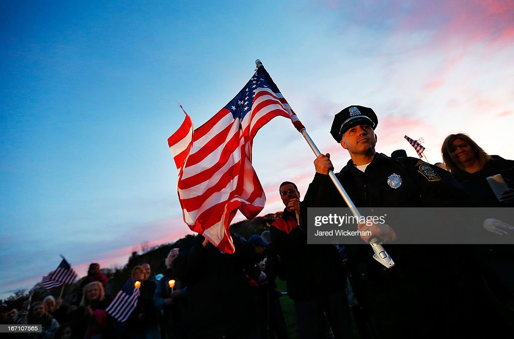 Watertown Police officer Brandon O'Neill holds up a large American flag during a candlelight vigil at Victory Park on April 20, 2013 in Watertown, Massachusetts. A manhunt for Dzhokhar A. Tsarnaev, 19, a suspect in the Boston Marathon bombing ended after he was apprehended on a boat parked on a residential property in Watertown, Massachusetts. His brother Tamerlan Tsarnaev, 26, the other suspect, was shot and killed after a car chase and shootout with police. The bombing, on April 15 at the finish line of the marathon, killed three people and wounded at least 170.