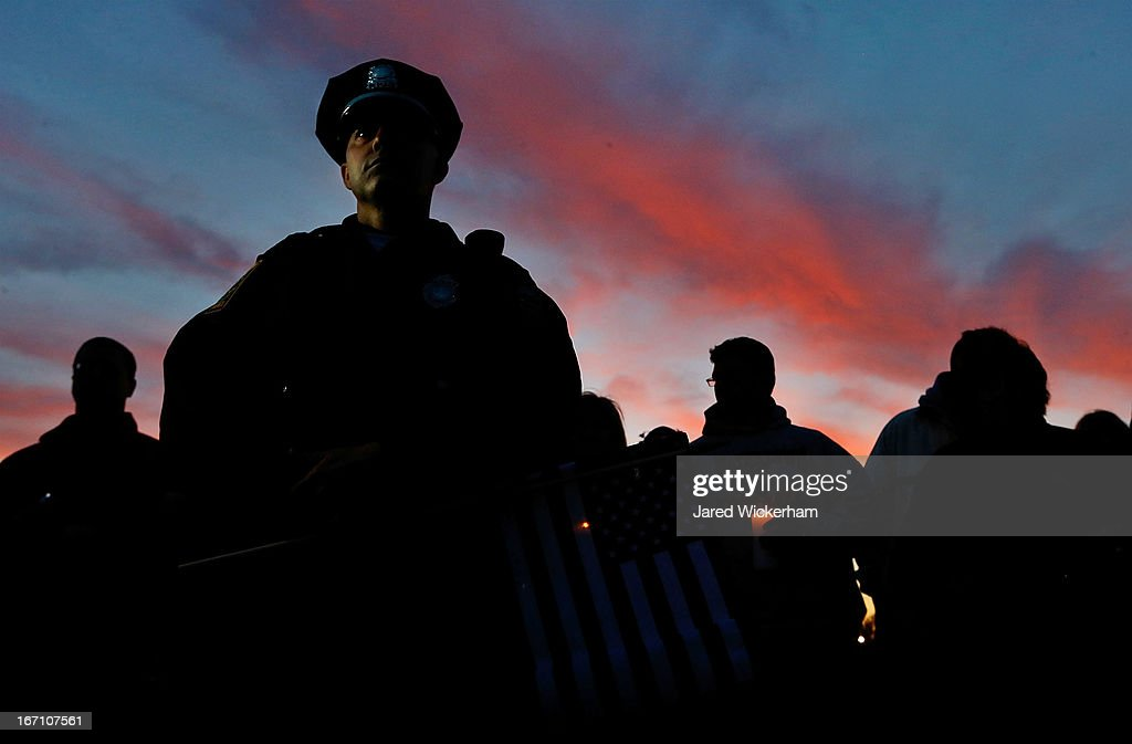Watertown Police officer Brandon O'Neill stands and listens to a pastor's words during a candlelight vigil at Victory Park on April 20 2013 in...
