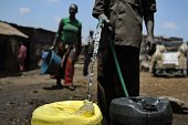 A watervendor collects water in jerrycans to sell on March 22 2012 in the Mathare slum Nairobi where a water shortage continues to bite on World...