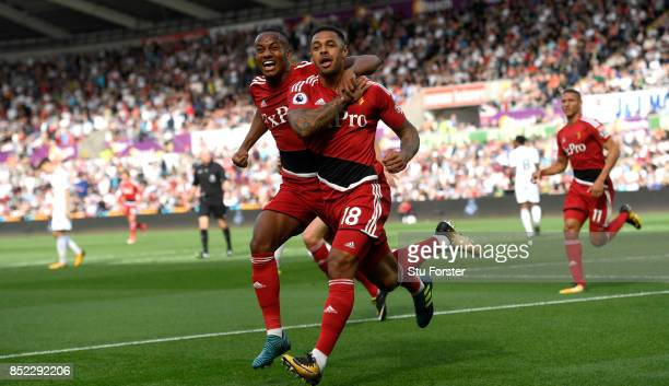 Watford striker Andre Gray celebrates with Andre Carrillo after scoring the opening goal during the Premier League match between Swansea City and...