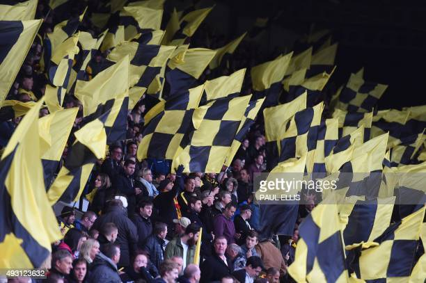 Watford supporters wave flags during the English Premier League football match between Watford and Arsenal at Vicarage Road Stadium in Watford north...