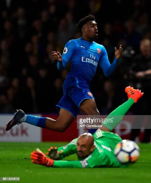 Watford's Brazilian goalkeeper Heurelho Gomes dives as Arsenal's Nigerian striker Alex Iwobi misses a chance during the English Premier League...