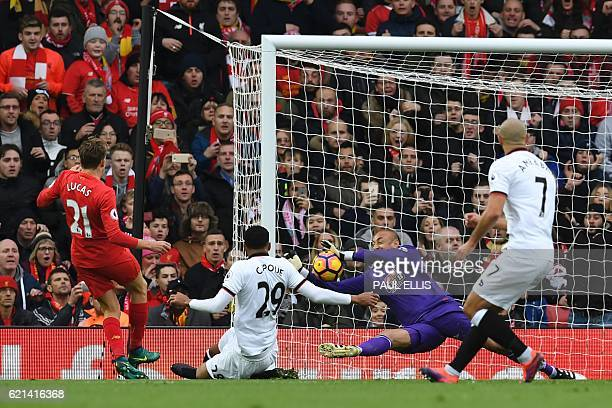 TOPSHOT Watford's Brazilian goalkeeper Heurelho Gomes saves a shot from Liverpool's Brazilian midfielder Lucas Leiva during the English Premier...