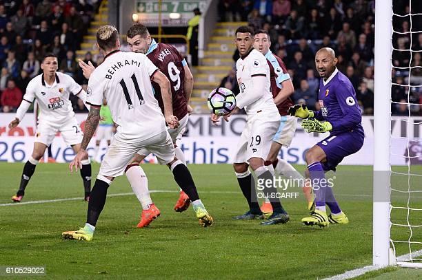 Watford's Brazilian goalkeeper Heurelho Gomes watches the ball bounce through the Watford defence from the head of Burnley's Irish midfielder Jeff...